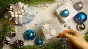 妇女` s手在与闪光灯和锥体顶视图的一张装饰的桌上把圣诞节被包裹的礼物放 股票录像