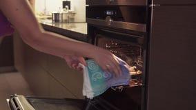 妇女` s手打开烤箱,采取被烧的曲奇饼,从被煮过头的食物来的烟 股票录像