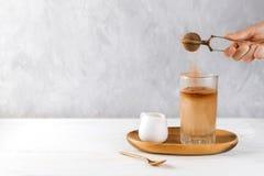妇女` s手打扫灰尘可可粉到素食主义者里冰了在一块高玻璃的咖啡在一个木盘子 免版税库存照片