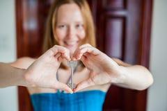 妇女` s手把握房子关键以在一个木门的背景的心脏的形式 拥有房地产概念 图库摄影