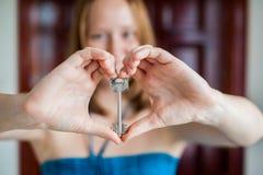 妇女` s手把握房子关键以在一个木门的背景的心脏的形式 拥有房地产概念 免版税库存照片