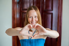 妇女` s手把握房子关键以在一个木门的背景的心脏的形式 拥有房地产概念 库存照片