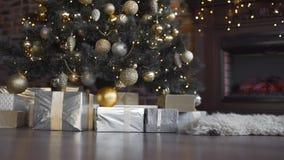 妇女` s手投入了有礼物的箱子在圣诞树、发光的圣诞树、诗歌选和球,新年` s下 股票视频