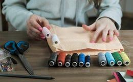 妇女` s手拾起螺纹的颜色对在圆点的橙色织品 关闭上色百合软的查阅水 免版税图库摄影