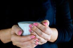 妇女` s手拿着一个杯子 免版税库存照片