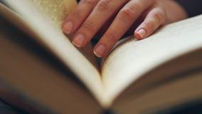 妇女` s手拿着一本书并且移动沿页的手指,当读时 股票录像