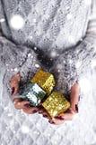 妇女` s手拿着圣诞节礼物盒 免版税库存图片