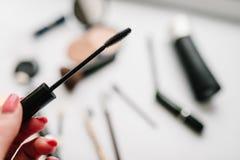 妇女` s手拿着染睫毛油的一把刷子在不同的化妆用品模糊的背景  复制空间,舱内甲板位置 顶视图 库存照片