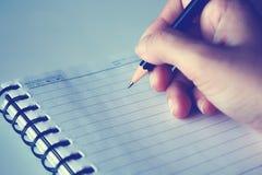 妇女` s手文字某事在笔记本 免版税库存照片