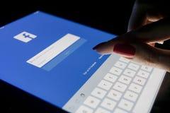 妇女` s手是在片剂苹果计算机iPad的触摸屏赞成在与Facebook主页网页的晚上 Facebook最大的社交 库存图片