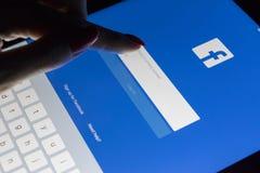 妇女` s手是在片剂苹果计算机iPad的触摸屏赞成在与Facebook主页网页的晚上 Facebook最大的社交 图库摄影