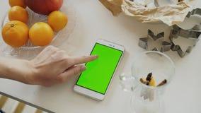 妇女` s手有绿色屏幕的浏览智能手机特写镜头在厨房用桌上在家 免版税库存照片