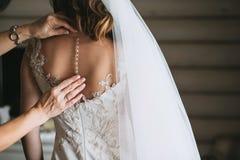 妇女` s手母亲改正了礼服在有美丽的被绣的面纱和按钮的一个新娘背面 图库摄影