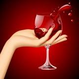 妇女` s手用在玻璃的红葡萄酒在深红背景 库存图片