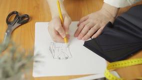 妇女` s手的特写镜头,衣裳时装设计师图画剪影在工作室 股票录像