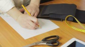 妇女` s手的特写镜头,衣裳时装设计师图画剪影在工作室 影视素材