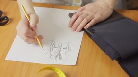 妇女` s手的特写镜头,衣裳时装设计师图画剪影在工作室 股票视频