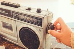妇女` s手被交换和调整按钮卡式磁带播放机的和记录器为听音乐 免版税库存照片