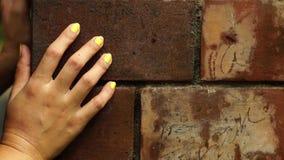 妇女` s手被握紧对砖墙 股票视频