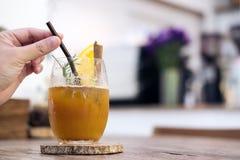 妇女` s手采摘秸杆的特写镜头图象在一杯的橙色冷的酿造咖啡 免版税图库摄影