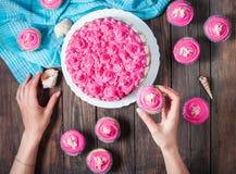 妇女` s手 蛋糕和杯形蛋糕与桃红色奶油在蓝色木背景 免版税库存照片