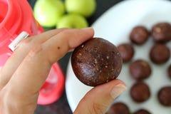 妇女` s手whith健康甜点特写镜头对待 烹调巧克力能量球用杏仁 免版税库存照片