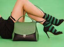 妇女` s提包和腿在黑nad绿色 图库摄影