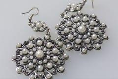 妇女` s服装jewelery 耳环由与石头的金属制成 白色表面上的谎言 在视图之上 免版税库存照片