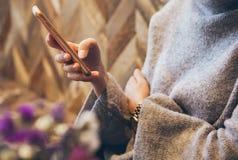 妇女` s特写镜头递固定的单元电话,当坐在与木墙壁时的现代咖啡 库存图片