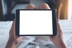 妇女` s的大模型图象递拿着有空白的桌面白色屏幕的黑片剂个人计算机,当在一张白色床上时 图库摄影