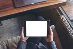 妇女` s的大模型图象递拿着有空白的白色屏幕的黑片剂个人计算机在与膝上型计算机的大腿 免版税库存图片