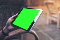 妇女` s的大模型图象递拿着有空白的绿色屏幕的黑片剂个人计算机在大腿 免版税库存图片