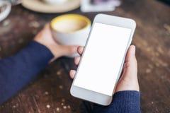 妇女` s的大模型图象递拿着有黑屏的白色手机在葡萄酒木头桌上 库存照片