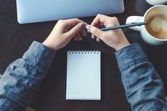 妇女` s的顶视图图象递拿着铅笔对写在有膝上型计算机和咖啡杯的一个空白的笔记本 库存图片