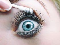 妇女` s眼睛吸引与棉花棒和手指法式修剪 宏指令 免版税库存图片