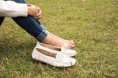 妇女` s脚和白色鞋子的关闭坐草地板 免版税图库摄影