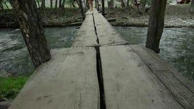 妇女` s腿沿在山河的一个狭窄的木桥走 野营和冒险概念 影视素材