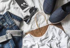 妇女` s衣物购买概念 牛仔裤,运动鞋,电话,太阳镜,在轻的背景的纸袋 免版税库存照片