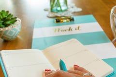 妇女` s被修剪的手特写镜头拿着绿松石的上色了在日期记事录的笔文字 库存照片