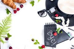 妇女` s辅助部件,夫人在度假 护照、笔记本和早餐新鲜的莓果、新月形面包和咖啡 奶油被装载的饼干 免版税库存图片
