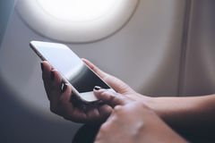 妇女` s递举行和指向有空白的黑桌面屏幕的一个白色巧妙的电话在飞机窗口旁边 免版税库存图片