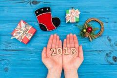 妇女` s递举行第2018个近的礼物盒和新年装饰品在蓝色老桌上 库存图片