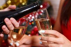 妇女` s递倾吐的香槟入玻璃,关闭  Celebrat 免版税库存照片