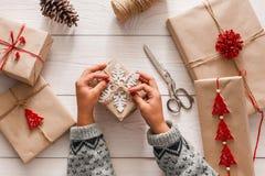 妇女` s递包裹当前圣诞节假日与工艺麻线 库存照片