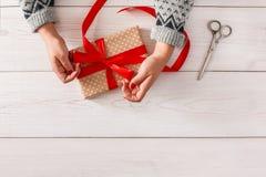 妇女` s递包裹当前圣诞节假日与红色丝带 免版税库存图片