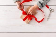 妇女` s递包裹当前圣诞节假日与红色丝带 免版税库存照片