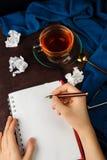 妇女` s递在一个笔记本的文字有与局促纸、玻璃和茶的空白页的或咖啡 库存照片
