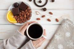 妇女` s递拿着一杯咖啡在一张木桌上的 顶视图 库存照片