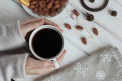妇女` s递拿着一杯咖啡在一张木桌上的 顶视图 图库摄影