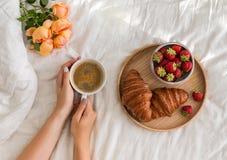 妇女` s递拿着一杯咖啡在床上的与白色床单 免版税库存图片